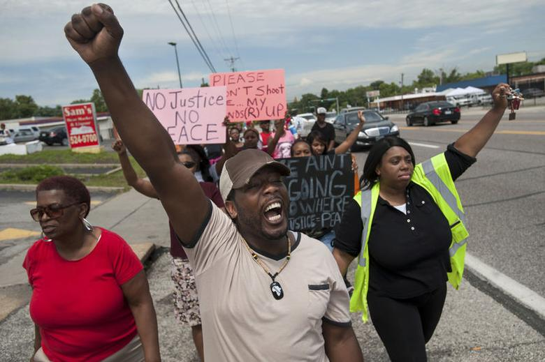 Protestors march down West Florissant Avenue in Ferguson, Missouri, August 19, 2014. REUTERS/Mark Kauzlarich