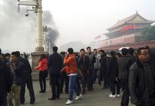 People walk along the sidewalk of Chang'an Avenue as smoke rises in front of the main entrance of the Forbidden City at Tiananmen Square in Beijing in this October 28, 2013 file photo. REUTERS/Stringer/Files
