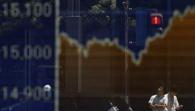 A man looks up as he is reflected on an electronic board displaying Japan's Nikkei average outside a brokerage in Tokyo August 11, 2014. REUTERS/Toru Hanai