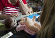 A young customer looks over the counter as a family member brings in a doll for repair at Sydney's Doll Hospital May 20, 2014. REUTERS/Jason Reed