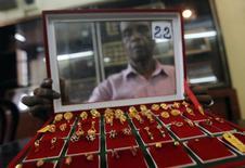 Продавец ювелирного магазина в Коломбо демонстрирует покупателю золотые сережки 2 декабря 2013 года. Цены на золото снижаются из-за укрепления доллара и ожиданий повышения процентных ставок ФРС. REUTERS/Dinuka Liyanawatte
