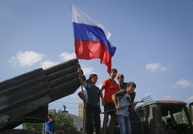 Children holding a Russian flag pose for photos on a destroyed Ukrainian army Grad multiple rocket launcher system that was seized and put on public display at the central square in Donetsk August 24, 2014. REUTERS/Maxim Shemetov