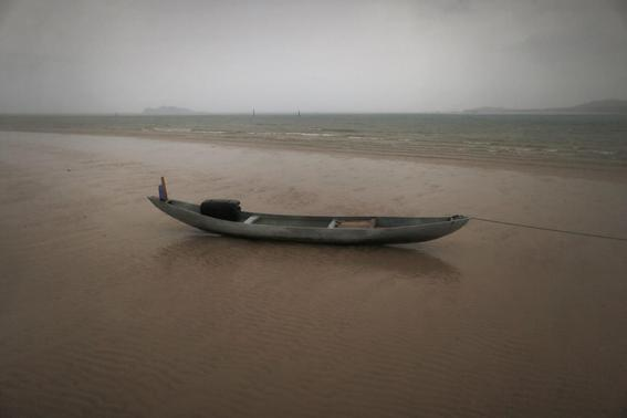 A fishing boat sits on a beach during a rain storm on the east coast of Natuna Besar July 7, 2014.   REUTERS-Tim Wimborne