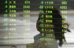Экран с котировками у брокерской конторы в Токио 11 апреля 2014 года. Азиатские фондовые рынки, кроме Южной Кореи, снизились во вторник, в основном под воздействием локальных факторов. REUTERS/Issei Kato
