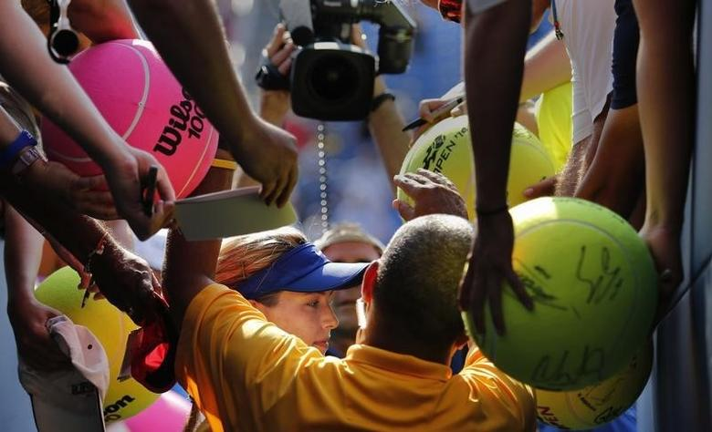 Canada's Eugenie Bouchard is mobbed for autographs after defeating Olga Govortsova of Belarus during their match at the 2014 U.S. Open tennis tournament in New York, August 26, 2014.    REUTERS/Eduardo Munoz