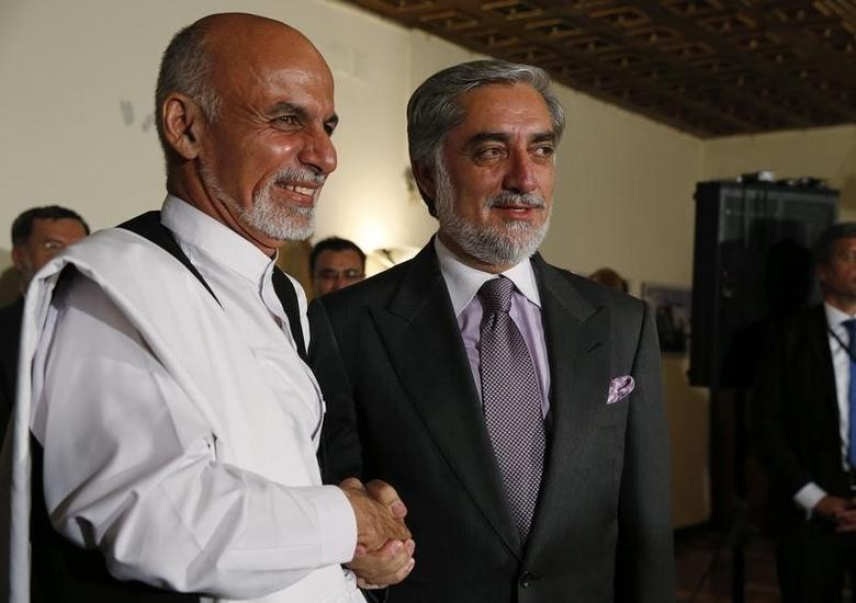 Afghanistan's presidential candidates Ashraf Ghani (L) and Abdullah Abdullah (R) shake hands after announcing a deal for the auditing of all Afghan election votes at the United Nations Compund in Kabul, July 12, 2014.  REUTERS/Jim Bourg