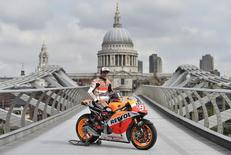 Honda MotoGP rider Marc Marquez of Spain poses on the Millennium Bridge with St Paul's Cathedral seen behind, in London, August 27, 2014. REUTERS/Toby Melville