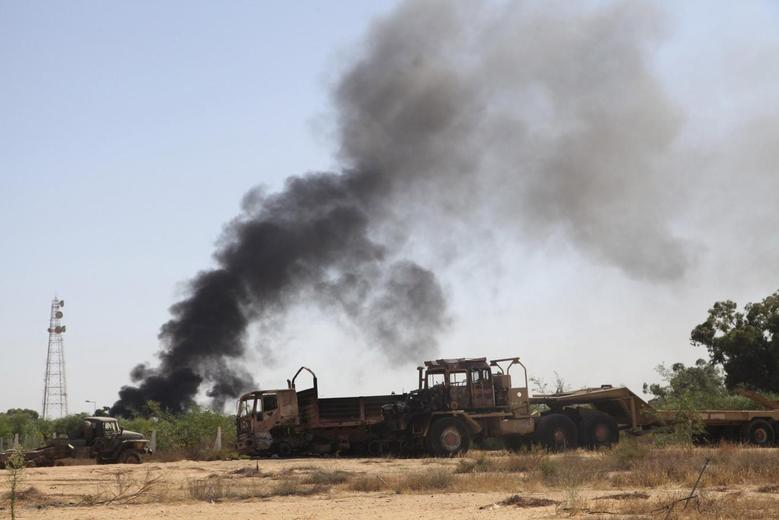 Smoke rises from the Brigade Qaqaa headquarters, a former Libyan Army camp known as Camp 7 April, following clashes between rival militias at the Sawani road district, August 24,2014. REUTERS/Stringer