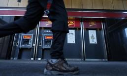 A pedestrian walks past the CIBC ATM machines in Montreal, April 24, 2014. REUTERS/Christinne Muschi