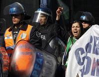 Una manifestante grita frases en contra del Gobierno cerca de policías antimotines, durante una protesta de trabajadores estatales que intentaban bloquear una calle en Buenos Aires, 27 de agosto del 2014. Sindicatos opositores y agrupaciones de izquierda protagonizaban el jueves la segunda huelga general del año contra el Gobierno de la presidenta argentina Cristina Fernández para reclamar mejoras salariales, en momentos de recesión económica y alta inflación. REUTERS/Enrique Marcarian