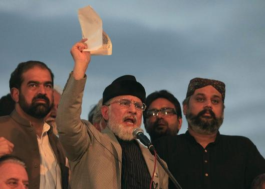Tahir ul-Qadri, Sufi cleric and leader of political party Pakistan Awami Tehreek (PAT), displays a document to supporters while speaking to them in front of the Parliament House building during the Revolution march in Islamabad August 28, 2014. REUTERS-Faisal Mahmood