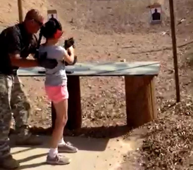 Shooting instructor Charles Vacca stands next to a 9-year-old girl at the Last Stop shooting range in White Hills, Arizona near the Nevada border, on August 25, 2014, in this still image taken from video courtesy of the Mohave County Sheriff's Office. REUTERS/Mohave County Sheriff's Office/Handout via Reuters