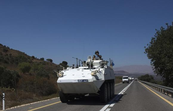 A member of the U.N. Disengagement Observer Force (UNDOF) rides atop an armoured vehicle near the Quneitra border crossing on the Israeli-occupied Golan Heights August 28, 2014.   REUTERS/Ronen Zvulun