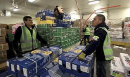 Unos trabajadores transportando flores de exportación en el aeropuerto El Dorado de Bogotá, feb 4 2014. El desempleo urbano en Colombia disminuyó a un 9,9 por ciento en julio, desde el 10 por ciento del mismo mes del año pasado, su nivel más bajo en nueve años, informó el viernes el Departamento Nacional de Estadísticas (DANE), en un reflejo de la fortaleza de la economía local. REUTERS/Jose Miguel Gomez