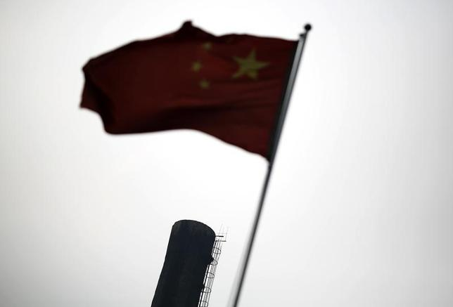 A Chinese national flag is seen in front of the chimney of a heat supply plant in Beijing July 16, 2014. REUTERS/Kim Kyung-Hoon