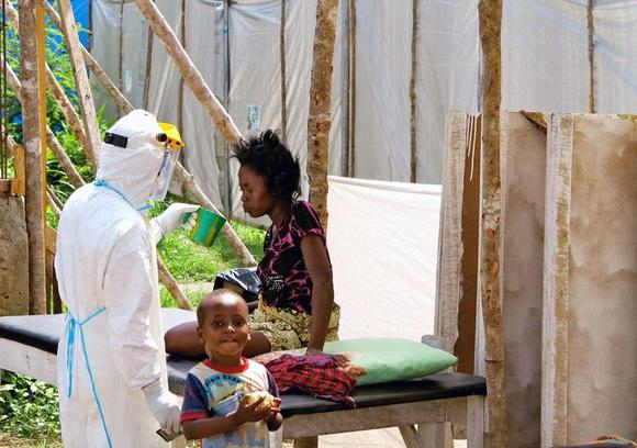 A health worker, wearing head-to-toe protective gear, offers water to a woman with Ebola, at a treatment centre for infected persons, as a young boy stands nearby in Kenema Government Hospital, in Kenema, Eastern Province, Sierra Leone, in this handout photo courtesy of UNICEF taken in July 2014.  REUTERS/Jo Dunlop/UNICEF/Handout via Reuters