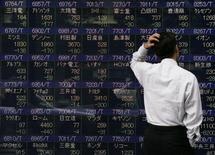 Мужчина изучает котировки на экране в Токио 8 октября 2008 года. Азиатские фондовые рынки, кроме Южной Кореи, незначительно выросли в понедельник под влиянием местных новостей.   REUTERS/Michael Caronna
