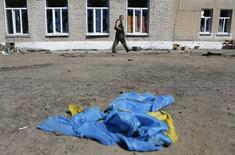 Пророссийский сепаратист проходит мимо лежащего на земле флага Украины в Иловайске 31 августа 2014 года. Потеряв за последние сутки семерых убитыми, украинские правительственные силы оставили сепаратистам аэропорт Луганска, который контролировали последние месяцы. REUTERS/Maxim Shemetov