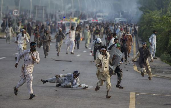 Anti-government protesters run after police personnel during the Revolution March in Islamabad September 1, 2014. REUTERS-Zohra Bensemra