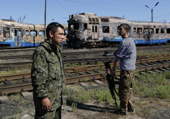 Pro-Russian separatists stand in front of destroyed trains at a railway station in the eastern Ukrainian town of Ilovaysk August 31, 2014. REUTERS/Maxim Shemetov