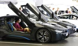 The world's first eight costumers of the new BMW i8 plug-in hybrid sports car receive instructions during the official delivery in Munich June 5, 2014.  REUTERS/Michaela Rehle