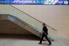 Человек проходит мимо электронного табло в здании Лондонской фондовой биржи 2 января 2013 года. Европейские фондовые рынки растут, пока инвесторы ждут решений Европейского центрального банка на совещании в четверг. REUTERS/Paul Hackett
