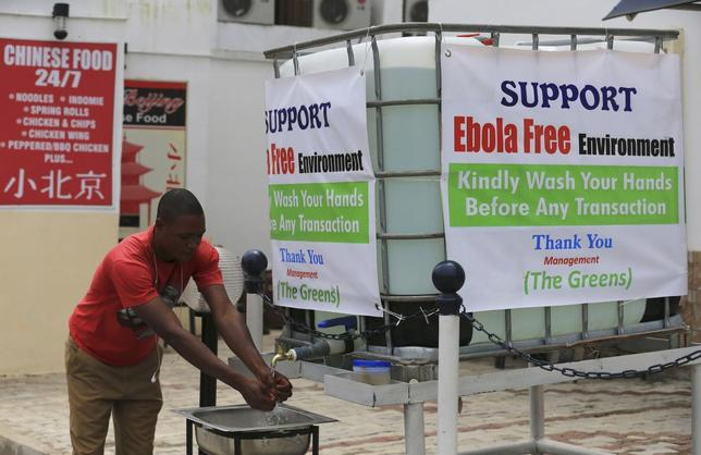 A man washes his hands at a tap outside the Green Pharmacy at Area 8 in Abuja, September 1, 2014.  REUTERS/Afolabi Sotunde