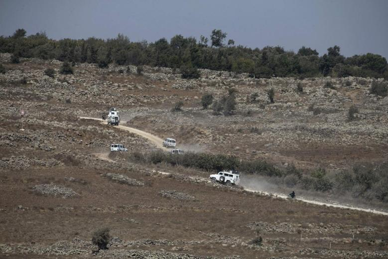 U.N. vehicles drive in Syria near the border fence with the Israeli-occupied Golan Heights September 2, 2014. REUTERS/Baz Ratner