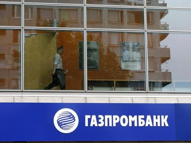 A person is pictured through a window above a Gazprombank branch in Moscow July 17, 2014. REUTERS/Sergei Karpukhin