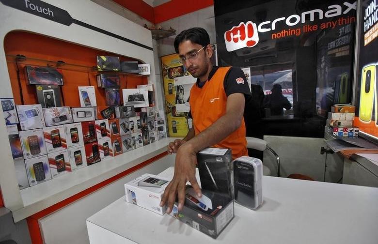 A worker displays a Micromax mobile phone inside a store in Kolkata December 4, 2013. REUTERS/Rupak De Chowdhuri