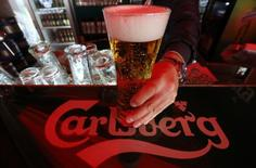A bartender holds a glass of Carlsberg beer in a bar in St. Petersburg June 17, 2014. REUTERS/Alexander Demianchuk