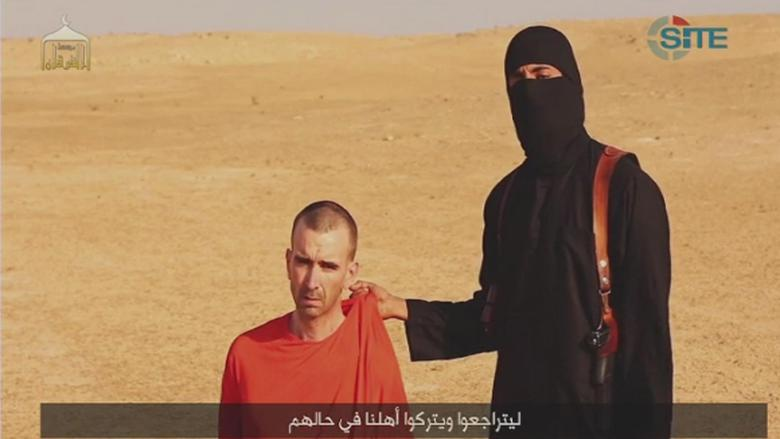 A video purportedly showing threats being made to a man Islamic State (IS) named as David Haines by a masked IS fighter in an unknown location in this still image from video released by Islamic State September 2, 2014.  REUTERS/Islamic State via Reuters TV