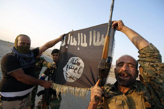 Iraqi Shiite militia fighters hold the Islamic State flag as they celebrate after breaking the siege of Amerli by Islamic State militants, September 1, 2014.  REUTERS-Youssef Boudlal