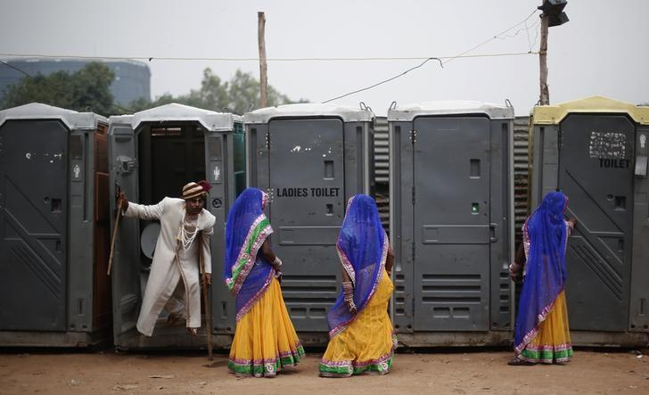 A groom comes out from a toilet as brides stand at the venue for a mass wedding ceremony at Ramlila ground in New Delhi June 15, 2014. REUTERS/Adnan Abidi