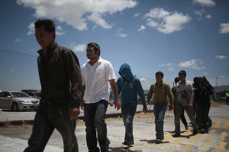Illegal migrants from Guatemala, deported from Phoenix, Arizona in the U.S., walk after arriving at an air force base in Guatemala City July 22, 2014. REUTERS/Jorge Dan Lopez