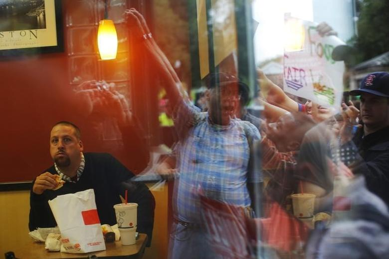 A man eats in a Burger King restaurant while demonstrators gather outside in Boston, Massachusetts August 29, 2013, part of a nation-wide fast food workers strike asking for $15 per hour wages and the right to form unions.  REUTERS/Brian Snyder