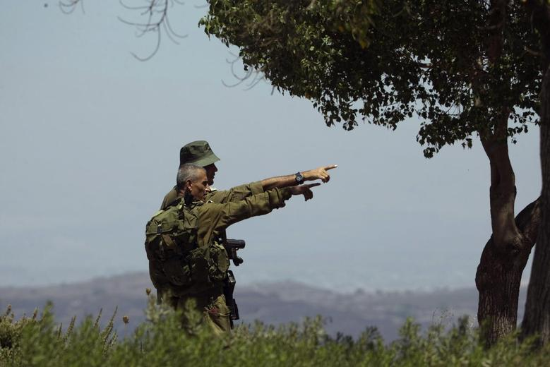 Israeli soldiers observe the Syrian side of the Quneitra border crossing between the Israeli-controlled Golan Heights and Syria, August 29, 2014. REUTERS/Ronen Zvulun