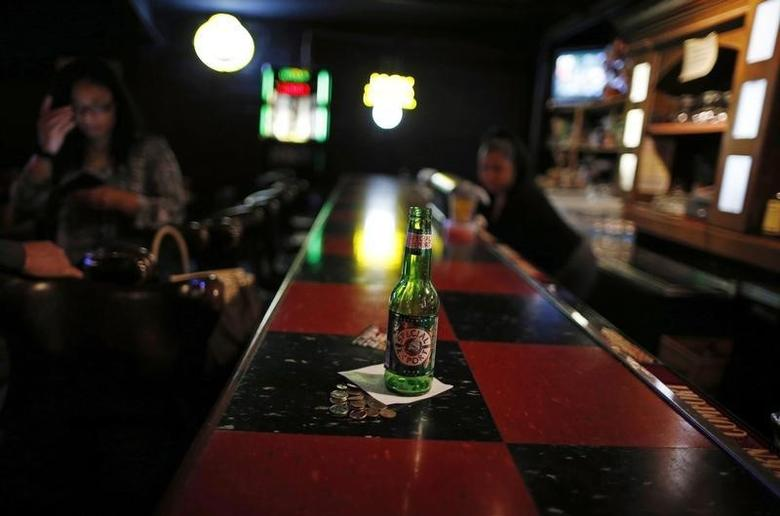 An empty beer bottle is seen on the bar at the Checkerboard Lounge in Chicago, Illinois, May 24, 2014.  REUTERS/Jim Young