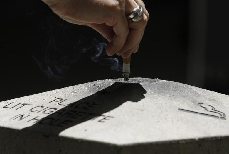 A woman disposes a cigarette in Los Angeles, California, May 31, 2012. REUTERS/Jonathan Alcorn