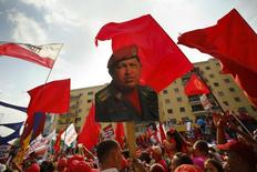 A supporter of Venezuela's President Nicolas Maduro holds up a picture of late president Hugo Chavez during a May Day demonstration in Caracas May 1, 2014. REUTERS/Jorge Silva
