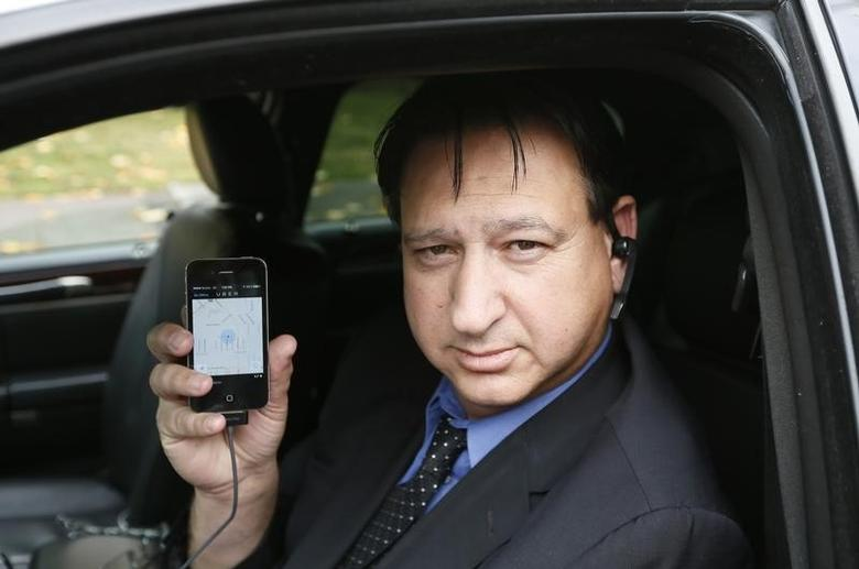 Limousine driver Shuki Zanna, 49, holds up his iPhone displaying transportation app Uber as he waits for customers in Beverly Hills, California, December 19, 2013.  REUTERS/Lucy Nicholson