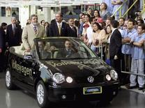 Brazil's then-President Luiz Inacio Lula da Silva (L, standing in car) rides with Sao Paulo State Governor Geraldo Alckmin in a Volkswagen Polo inside an assembly plant, during a visit to celebrate the company's 50th anniversary of production in Brazil, in Sao Bernardo do Campo, in this March 24, 2003 file photo. REUTERS/Jose Patricios/Files