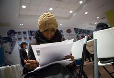 Una mujer rellena unas aplicaciones en una feria de empleo en Coney Island en Nueva York, dic 11 2013. Las contrataciones por parte de los empleadores de Estados Unidos bajaron en agosto al menor nivel en ocho meses, al tiempo que creció el número de personas que abandonaron la búsqueda de un puesto de trabajo, dando a una cautelosa Reserva Federal más motivos para esperar antes de subir las tasas de interés. REUTERS/Eric Thayer