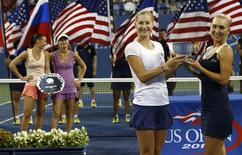Ekaterina Makarova and Elena Vesnina (R), both from Russia, hold their trophy after defeating Martina Hingis of Switzerland and Flavia Pennetta of Italy (rear, L) in the women's doubles final match at the 2014 U.S. Open tennis tournament in New York, September 6, 2014.      REUTERS/Mike Segar