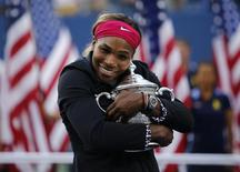 Serena Williams of the U.S. embraces her trophy after defeating Caroline Wozniacki of Denmark in their women's singles finals match at the 2014 U.S. Open tennis tournament in New York, September 7, 2014. REUTERS/Eduardo Munoz