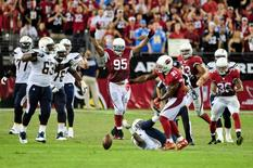 Sep 8, 2014; Glendale, AZ, USA; Arizona Cardinals defensive end Tommy Kelly (95) and teammates celebrate after stopping the San Diego Chargers on 4th down during the second half at University of Phoenix Stadium. Mandatory Credit: Matt Kartozian-USA TODAY Sports