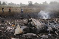 """Сотрудники чрезвычайных служб на месте крушения самолета  Boeing 777 авиакомпании Malaysia Airlines близ Грабово 17 июля 2014 года. Пассажирский самолет малайзийских авиалиний, летевший рейсом МН17, потерпел крушение на востоке Украины в июле из-за воздействия на него """"большого количества объектов с высокой энергией"""". REUTERS/Maxim Zmeyev"""