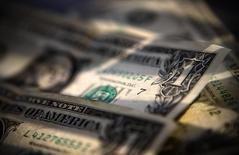 Долларовые купюры в Торонто 26 марта 2008 года. Доллар поднялся до шестилетнего максимума к иене и 14-месячного пика к корзине валют во вторник, после того, как исследование ФРС заставило инвесторов переоценить перспективы повышения ключевой ставки.  REUTERS/Mark Blinch