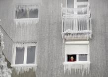 Женщина выглядывает из окна дома в Постойне, Словения 5 февраля 2014 года. С приближением зимы власти европейских стран готовятся к экстренным мерам на случай остановки поставок российского газа, но некоторые трейдеры делают ставку на снижение цен, не видя большого риска перебоев. REUTERS/Srdjan Zivulovic