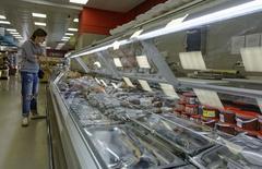 Женщина у прилавка магазина во Владивостоке 7 сентября 2014 года. Инфляция в России за период со 2 по 8 сентября ускорилась до 0,2 процента, а с начала года составила 5,8 процента, сообщил Росстат. REUTERS/Yuri Maltsev